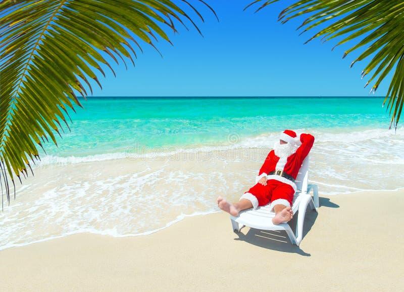 Рождество Санта Клаус ослабляет в sunlounger на тропическом песочном Palm Beach стоковая фотография