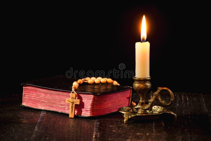 Розарий на книге, и освещенная свеча в подсвечнике стоковая фотография rf