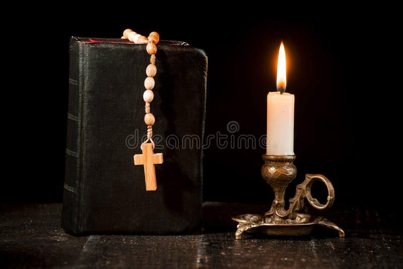 Розарий на книге, и освещенная свеча в подсвечнике стоковое изображение rf