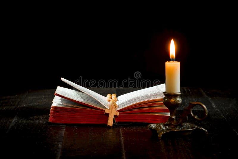Розарий на книге, и освещенная свеча в подсвечнике стоковые изображения