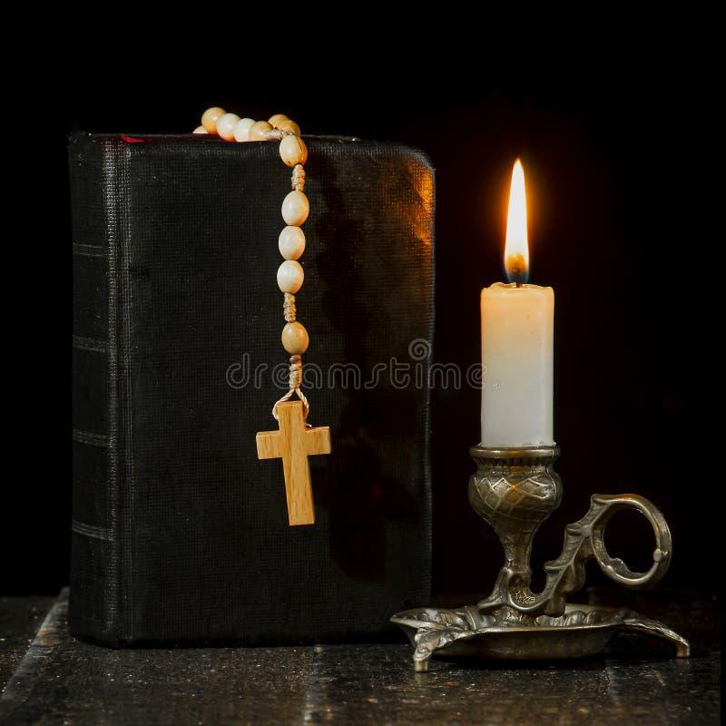 Розарий на книге, и освещенная свеча в подсвечнике стоковые фотографии rf