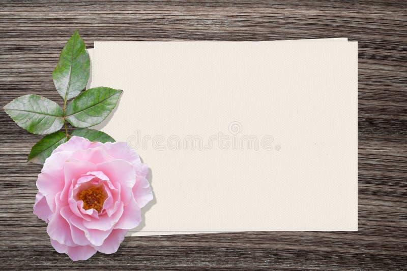 Роза пинка и и бумага на деревянной предпосылке стоковая фотография rf