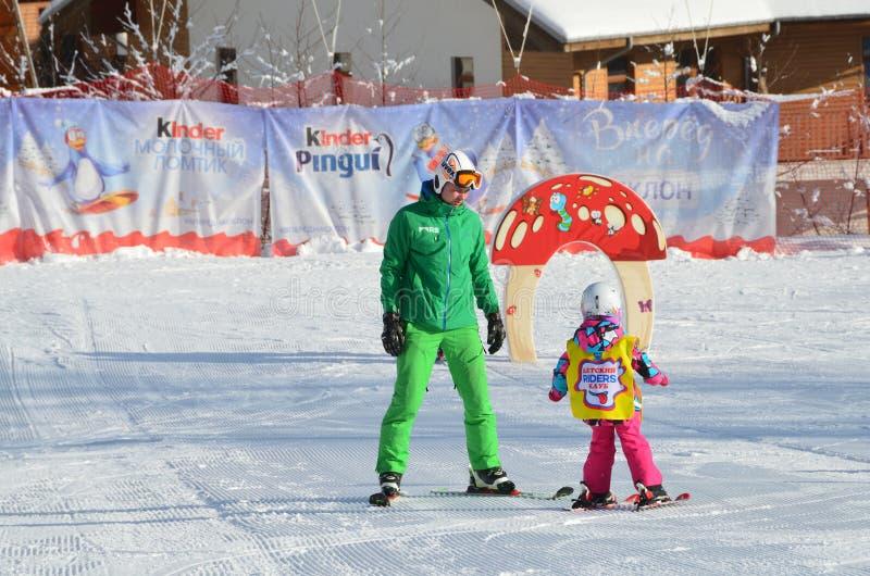 Роза Khutor, Сочи, Россия, 26-ое января 2018 Маленькая девочка инструктора уча, который нужно кататься на лыжах на наклоне тренир стоковые фото