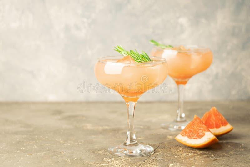 Розмариновое масло и лед грейпфрута напитка 2 элегантных стеклянных кубка на серой конкретной предпосылке Освежая коктейль лета стоковые изображения rf