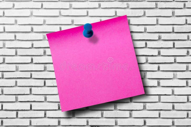 Розовая бумага примечания на белой предпосылке кирпичной стены стоковое фото rf