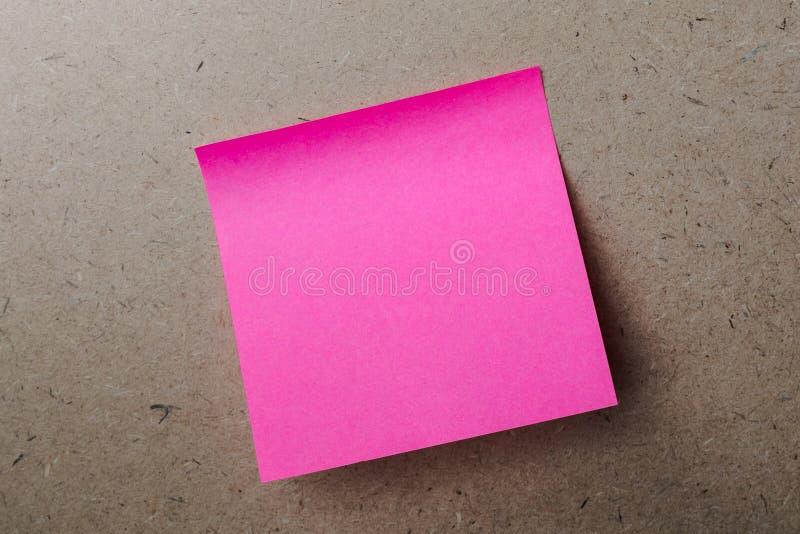 Розовая бумага примечания на деревянной доске как предпосылка стоковое фото