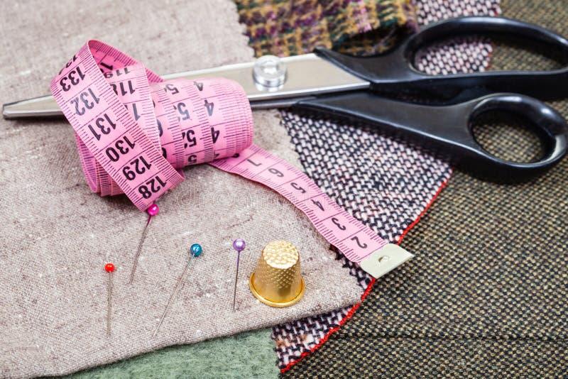 Розовая лента измерения, штыри, кольцо, ножницы на ткани стоковые фото