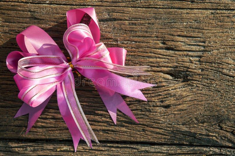 Розовая лента украшенная на текстурированной древесине стоковые фотографии rf