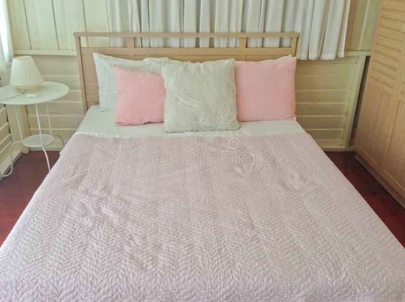 Розовая и белая подушка, розовое одеяло в деревянном interi помадки спальни стоковые изображения rf
