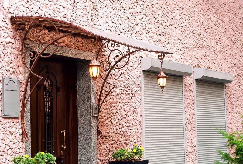 Розовая каменная стена с винтажной деревянной дверью Брайна с фонариками, цветочными горшками и декоративной вковкой Дизайн, есте стоковая фотография rf