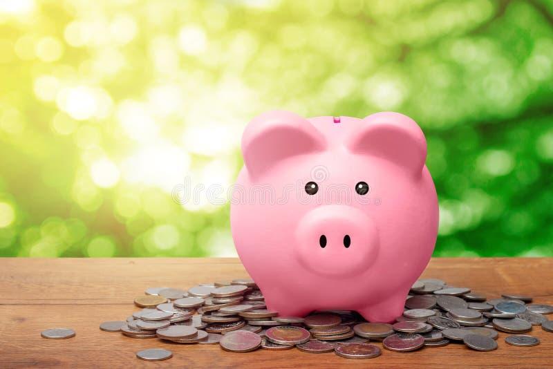Розовая копилка стоя над кучей монеток на деревянном столе стоковое изображение rf