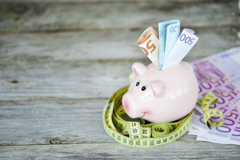 Розовая копилка с банкнотами евро и лента измерения на деревянном столе стоковая фотография rf