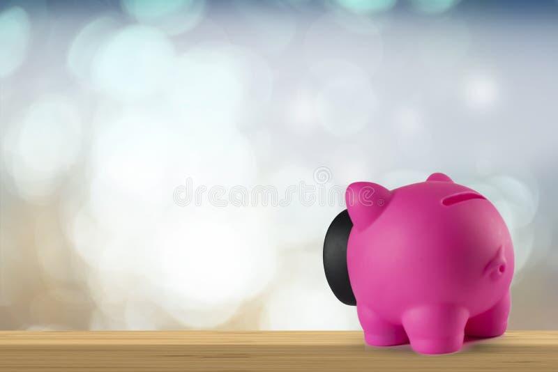 Розовая копилка на деревянной столешнице стоковые фотографии rf