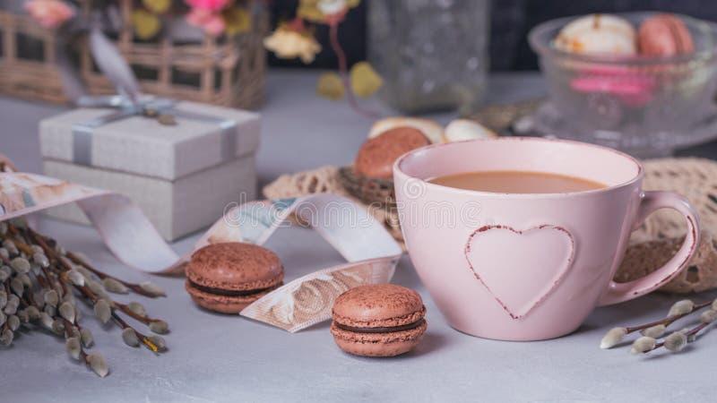 Розовая кружка кофе с сладостными пастельными французскими macaroons, подарочная коробка и стоковое фото