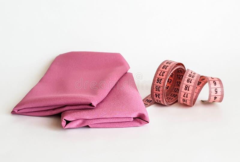 Розовая лента измерения с черными номерами на белой предпосылке естественных или ткани Близкий поднимающий вверх взгляд измеряя л стоковые изображения