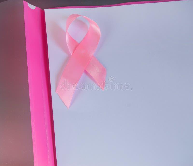 Розовая лента на листе бумаги для того чтобы поднять осведомленность рака молочной железы, космоса экземпляра, взгляда сверху стоковые изображения