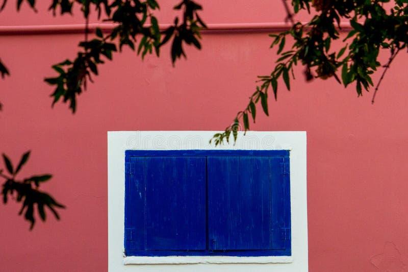 Розовая пастельная стена традиционного здания с голубым деревянным ветром стоковое фото