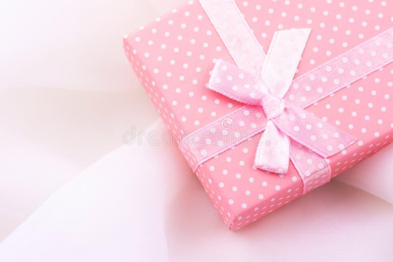 Розовая подарочная коробка связанная с лентой сатинировки с смычком на чувствительной белой предпосылке ткани, романтичной, вален стоковое изображение