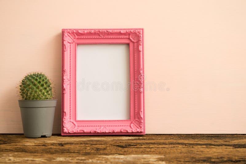 Розовая рамка фото на старом деревянном столе с кактусом над розовой стеной стоковое изображение rf