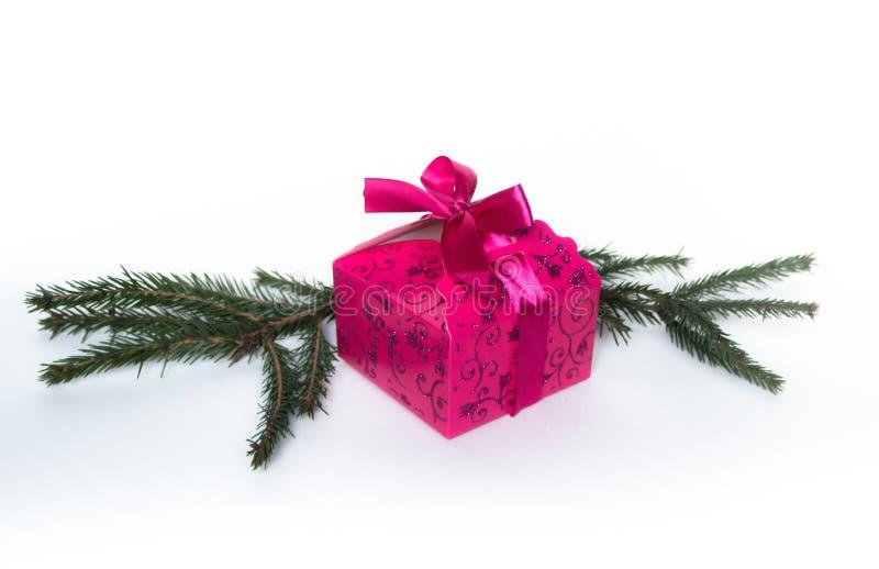 Розовая сияющая подарочная коробка с елевой ветвью на белой предпосылке стоковое изображение