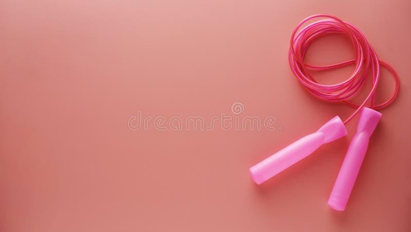 Розовая скача веревочка или прыгая веревочка изолированная на розовой предпосылке Спорт, фитнес, cardio, здоровая концепция разми стоковые фото