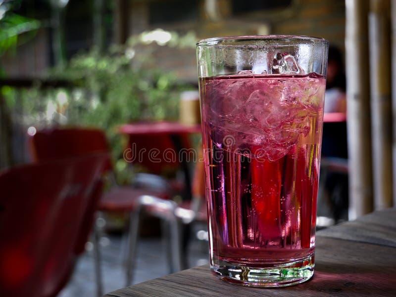 Розовая сода с льдом на стекле помещенном на таблице в ресторане стоковое изображение rf