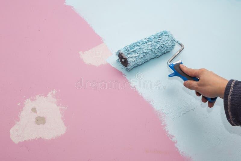 Розовая стена комнаты младенца покрашена голубой с рукой и роликом стоковая фотография rf