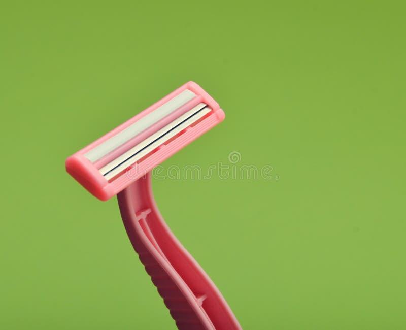 Розовая устранимая бритва для депиляции на зеленой предпосылке стоковые изображения rf