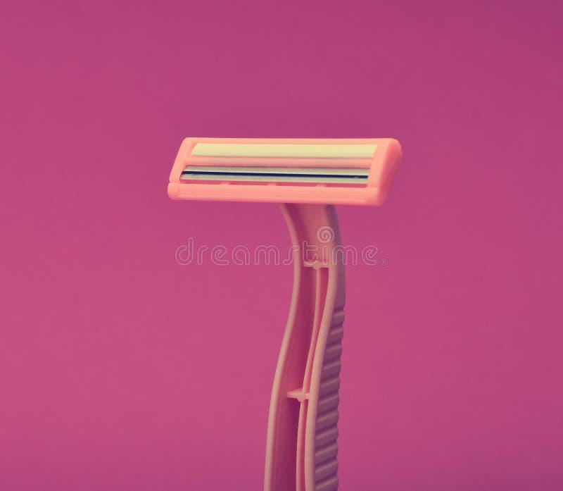 Розовая устранимая бритва для депиляции на розовой предпосылке стоковое фото