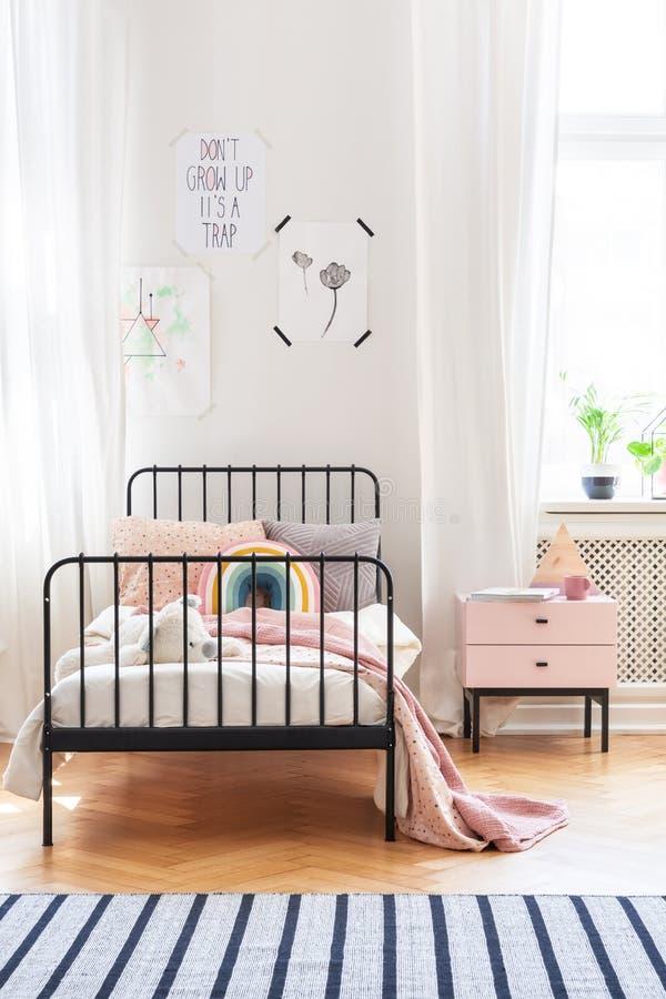 Розовое одеяло на кровати рядом с шкафом в ярком интерьере спальни ` s ребенк с плакатами и ковром стоковые изображения rf
