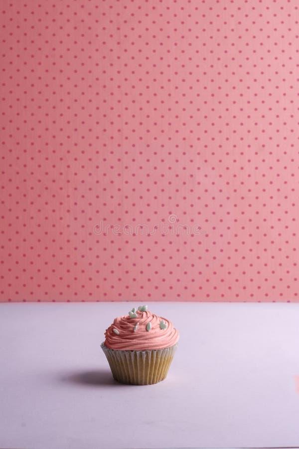 Розовое пирожное с взбитой сливк, и сердце брызгают на поставленный точки стоковое фото