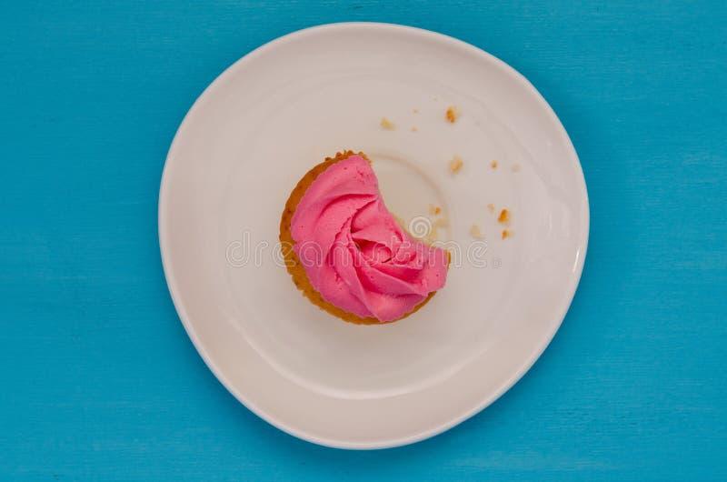 Розовое сдержанное пирожное на плите изолированной на голубой предпосылке Очень вкусный торт r стоковое фото