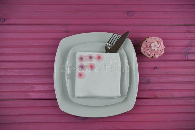 Розовое урегулирование места расписания пасхи в белизне с замороженными цветками и розовым домодельным пирожным с космосом стоковые изображения rf