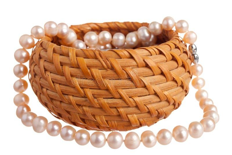 Розовое nacklace перлы в корзине стоковые изображения