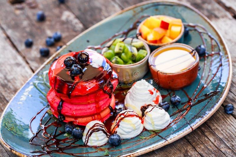 Розовые блинчики withaPink блинчиков с медом, шоколадом, вареньем, взбитой сливк, ягодами и плодами на плите стоковое изображение rf