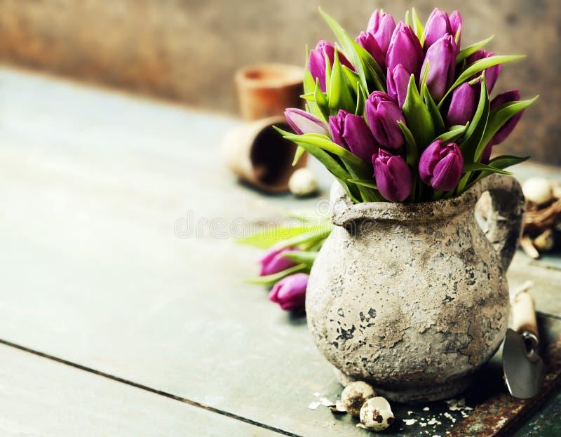 Розовые букет тюльпанов, пасхальные яйца и садовые инструменты стоковое изображение