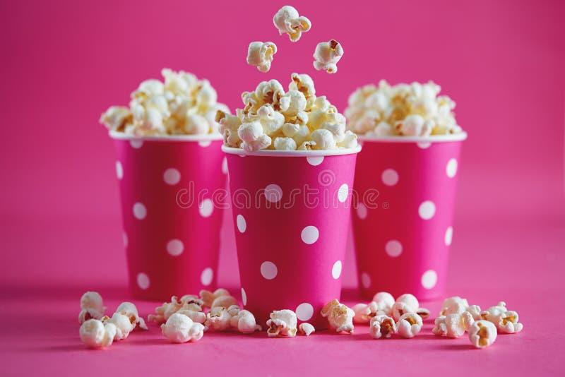 Розовые бумажные стаканчики точки польки с вкусным попкорном стоковое изображение