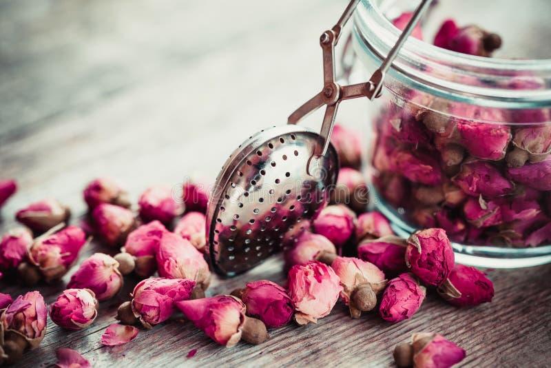 Розовые бутоны чай, infuser чая и стекло раздражают стоковое изображение rf