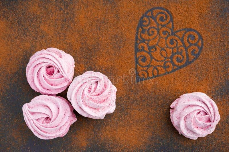 Розовые домодельные зефиры и земной циннамон как предпосылка на праздник дня Валентайн стоковое изображение rf