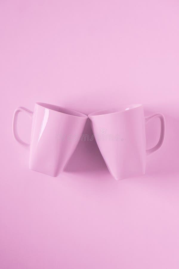Розовые кружки кофе на розовой предпосылке clinking в приветственных восклицаниях с пустым copyspace стоковое фото rf