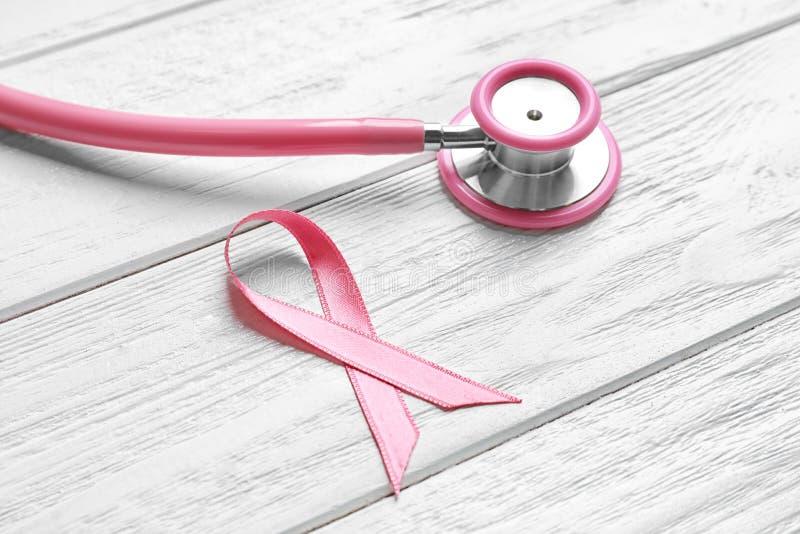 Розовые лента и стетоскоп на светлой деревянной предпосылке стоковое изображение rf