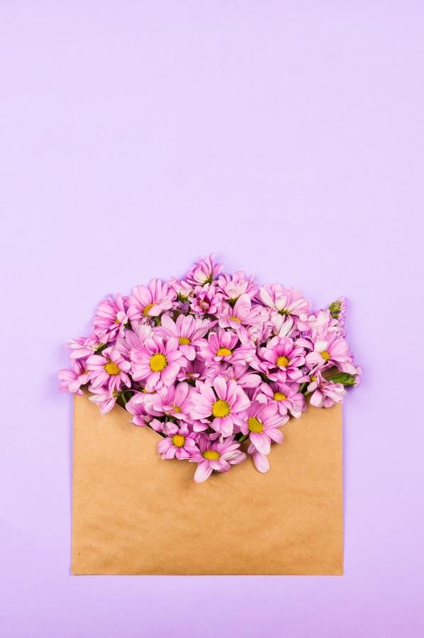 Розовые маргаритки в винтажном коричневом конверте, flatlay стоковые изображения rf