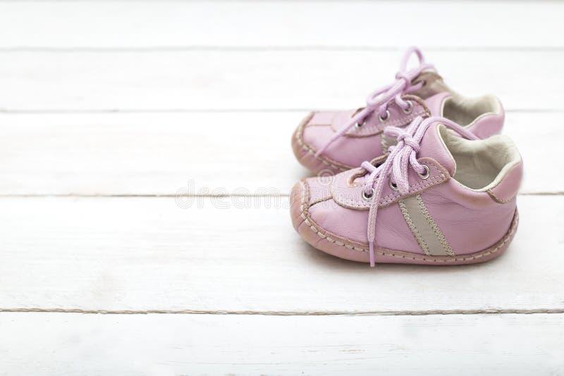 Розовые маленькие ботинки для девушки на белой деревянной предпосылке стоковые изображения rf