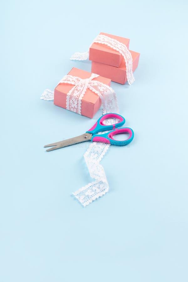 Розовые подарочные коробки со шнурком и ножницы на голубой предпосылке цвета Минимальная предпосылка обруча подарка стоковые фото