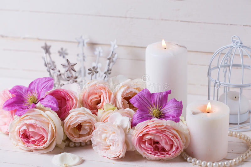 Розовые розы и фиолетовый clematis цветут, свечи на белизне сватают стоковые изображения rf