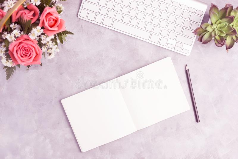 Розовые розы на серой таблице с белой клавиатурой и открытой тетрадью стоковое изображение