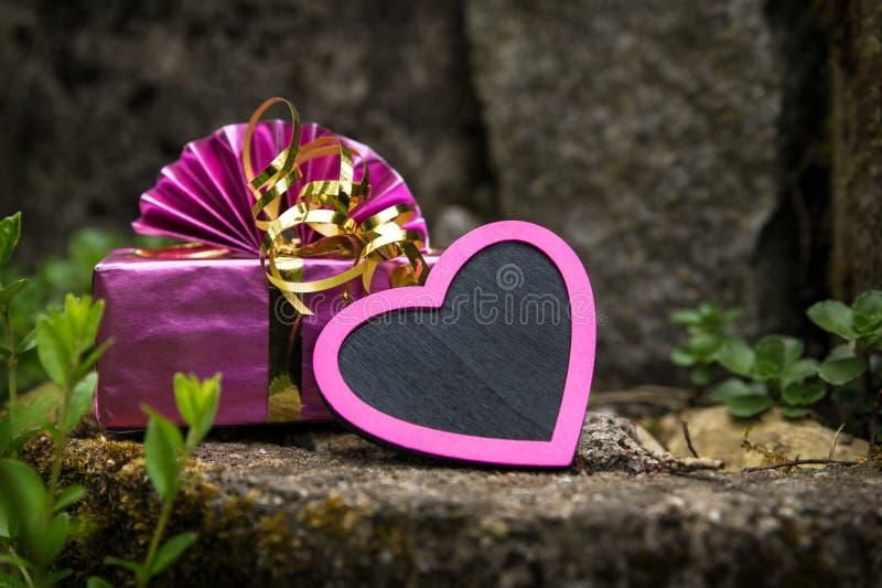 Розовые сердце и настоящий момент на винтажном rockery стоковое фото