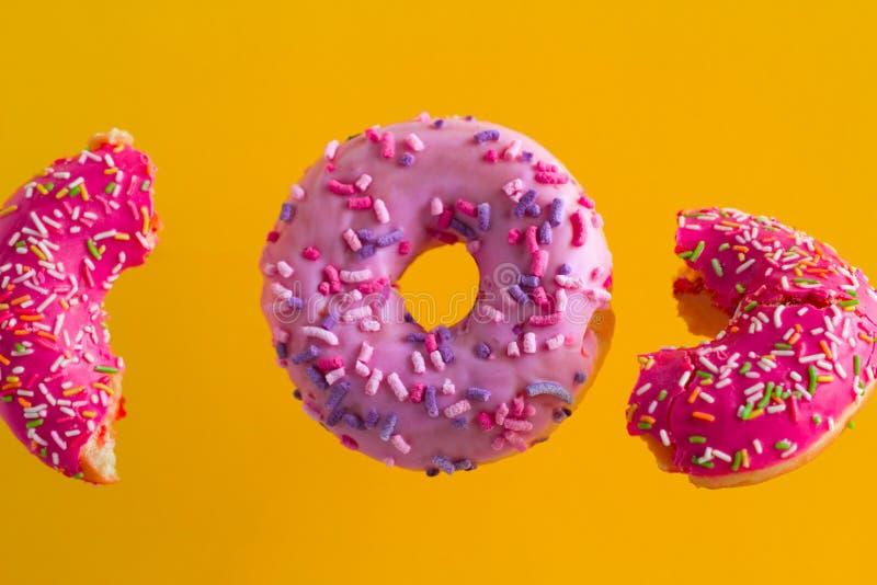 розовые сладкие donuts с брызгают на живой желтой предпосылке стоковое фото rf