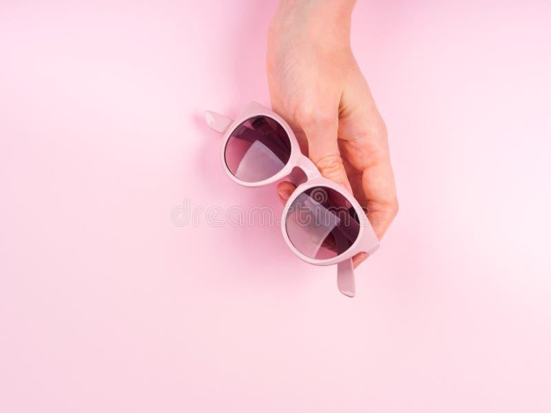 Розовые солнечные очки в руке женщины стоковое фото
