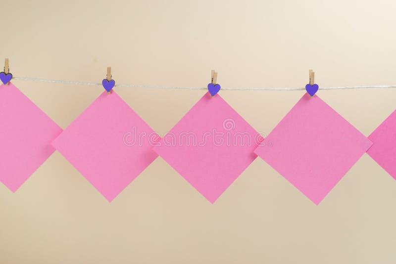 Розовые стикеры на веревке для белья с зажимками для белья изолированными на белой предпосылке стоковая фотография rf